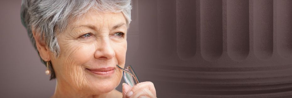 Elderly woman holding glasses looks off in distance