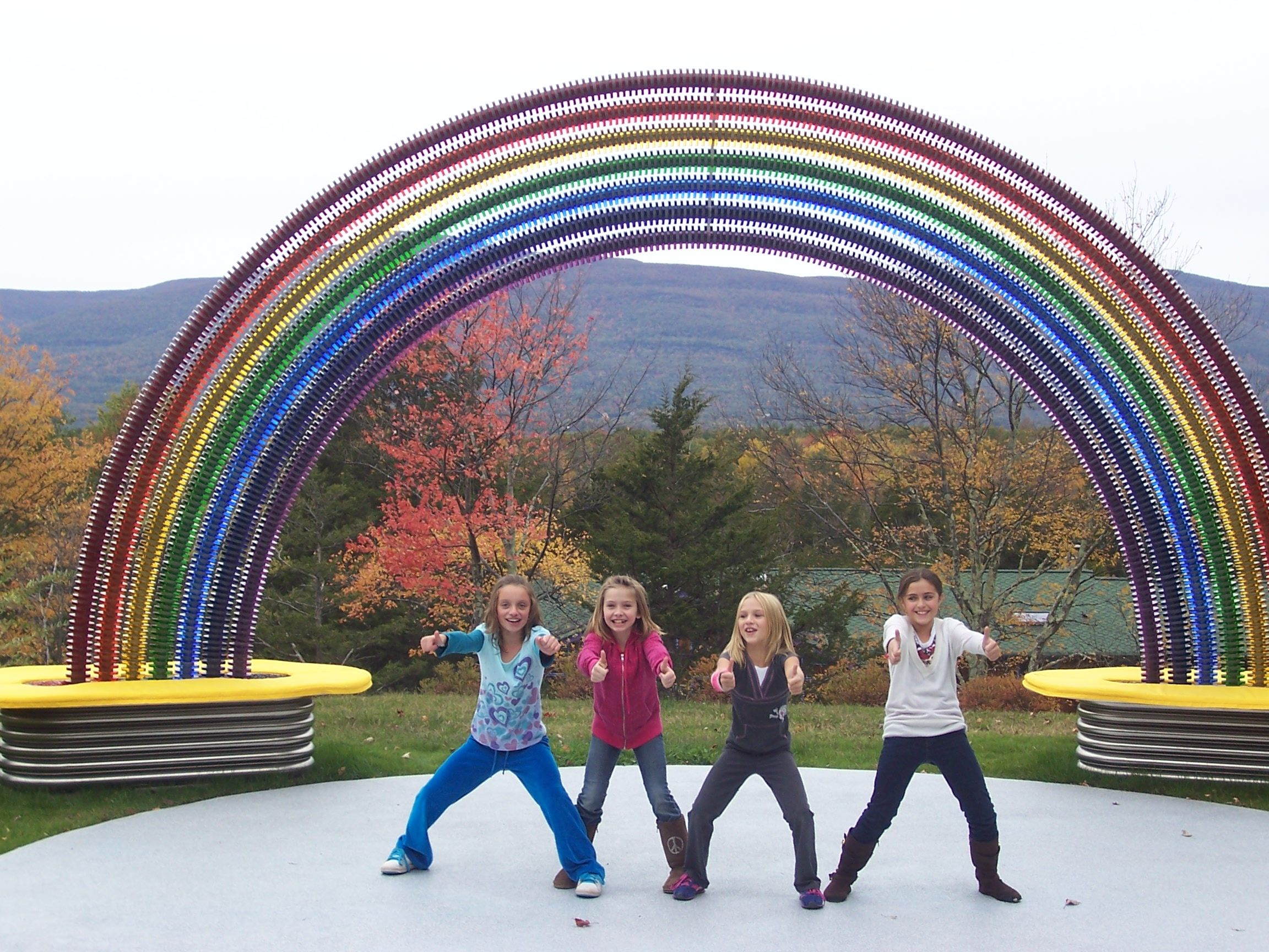 Children giving thumbs up in front of the rainbow sculpture at Tischler Dental