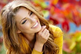 Woman in yellow sweater smiling while looking off into the distance