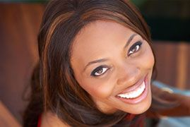 African American woman show off her smile after having her gums reshaped.