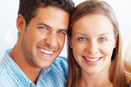 A young couple with healthy gums smiles together