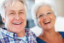 An older couple laughs together after receiving dental crowns