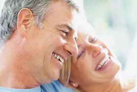 An older couple laughs together after having smile makeovers