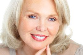 an older woman smiles brightly after receiving dental implants