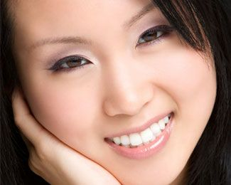 A young Asian woman with bright white teeth