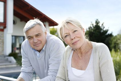 Older couple sitting in front of home