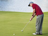 A man is concentrating while putting a golf ball.