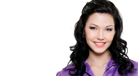 A fair-skinned woman with dark brown hair and a purple shirt smiles.