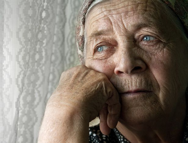 Elderly woman looking sadly out window
