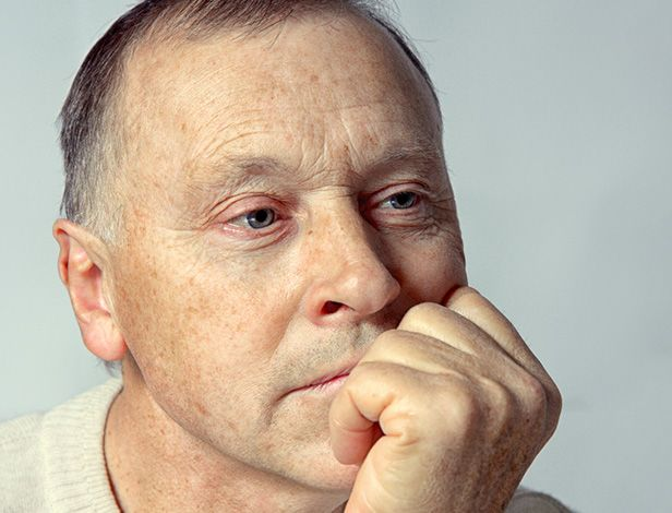 Contemplative older man holding knuckles to mouth