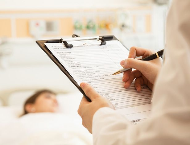 Nurse writing on clipboard in front of hospital patient