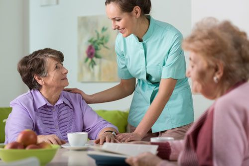 Nurse speaking with women at nursing home