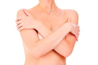 A woman crosses her arms over her breasts