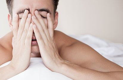 Man rubbing his face tiredly in bed