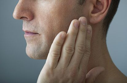 Man gently touching corner of his jawbone