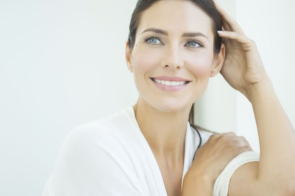 A brown haired woman in her forties smiles after getting dermal fillers