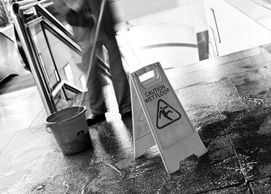 Slippery floor sign and blurred image of man mopping