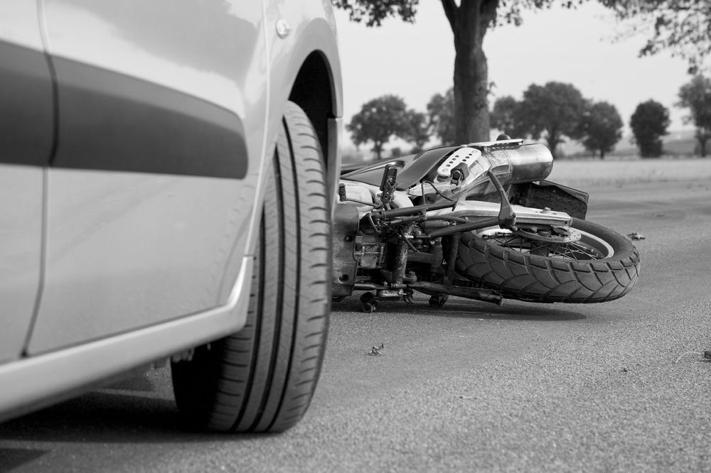 The front of a car in front of a wrecked motorcycle