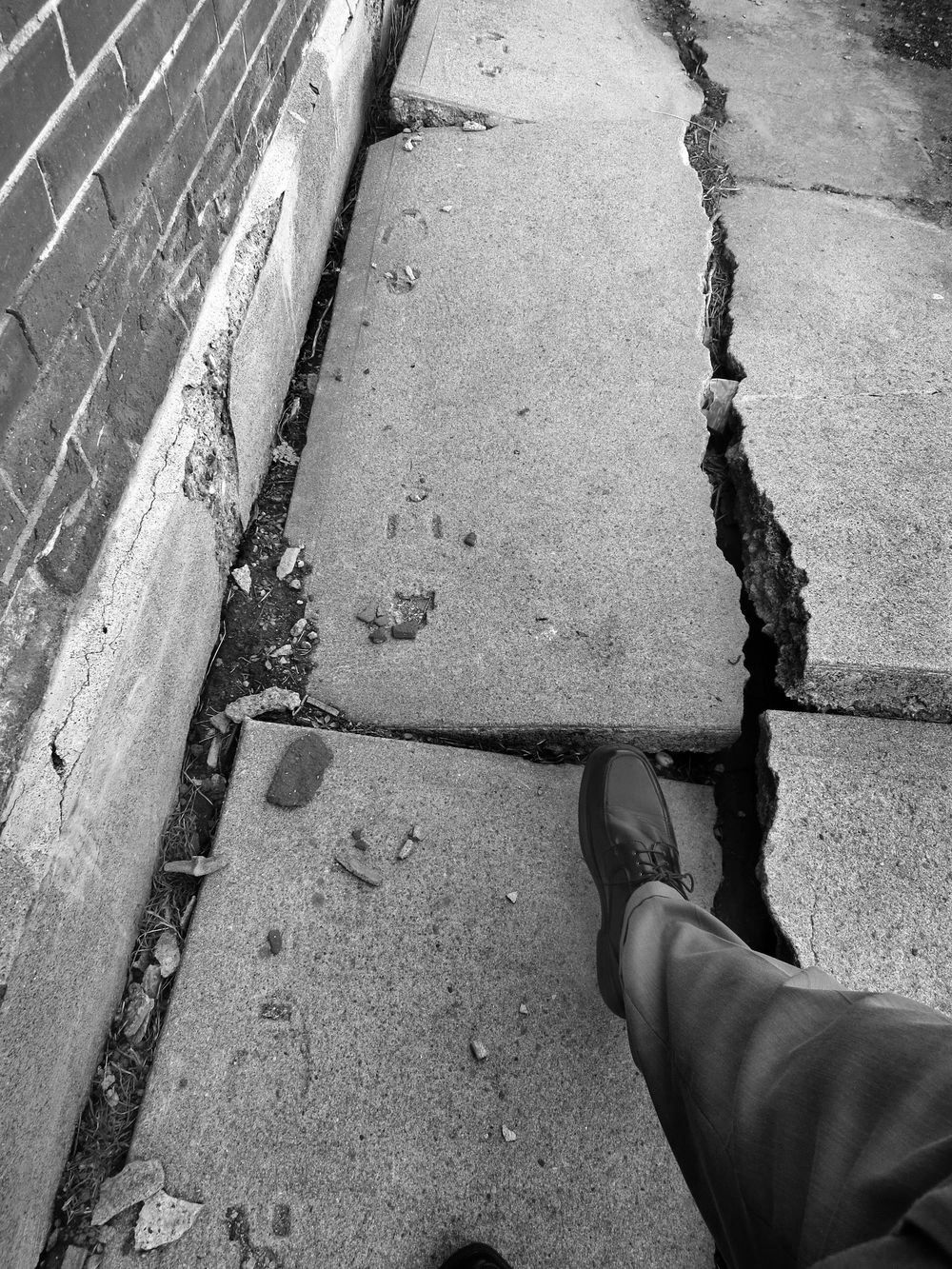 A first person view of a pedestrian walking on a cracked sidewalk