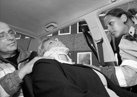 A woman wears a neck brace while receiving emergency medical care from two healthcare workers.