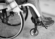A closeup of a paraplegia victim's legs and arms as he moves the wheels.