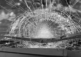 A windshield that has been broken into a spiderweb shape from blunt force.