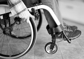 A closeup view of a wheelchair as hands move the wheels and feet rest.