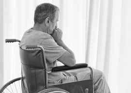 A man sits in a manual wheelchair facing a window, concerned, with his hands clasped to his face.