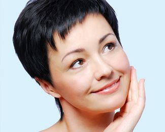 A young woman with a short, black pixie haircut holds her face and looks kindly to the side.
