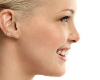 A closeup profile of a young, white woman with blonde hair who has two piercings in her ear.