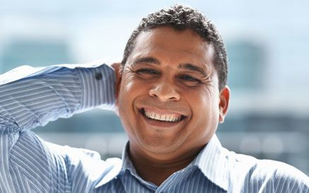 Hispanic man wearing a striped shirt smiles while resting his hand on his head