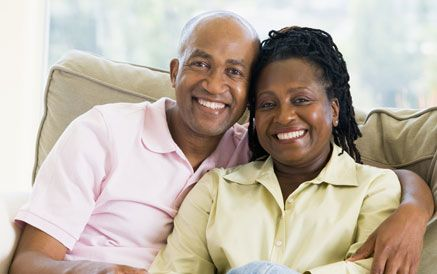 African American husband and wife smiling while sitting on the couch