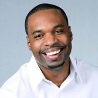 African American man wearing a white shirt smiling