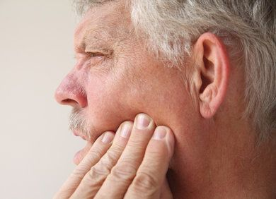 Elderly man clutching jaw in pain