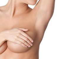 A woman covers her breast with her right hand