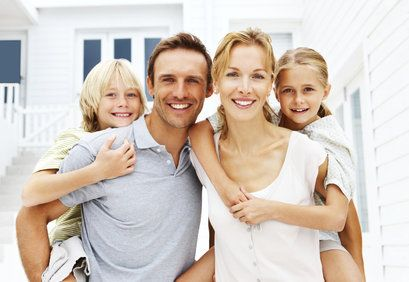 Smiling parents piggybacking two small children