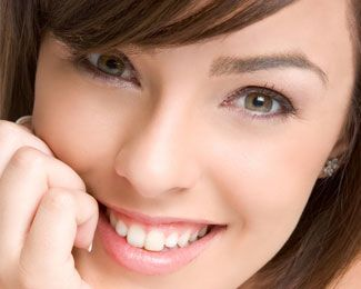 Brunette female smiling following teeth whitening treatment