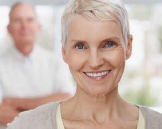 Elderly woman with short gray hair smiling