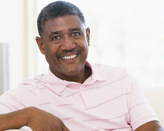 African American male smiling while lounging on a white chair