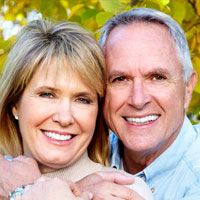 An older couple shows off their all-on-four dental implants