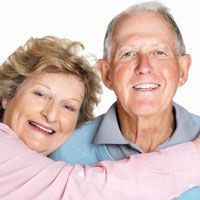 an older couple smiles with their natural-looking dentures