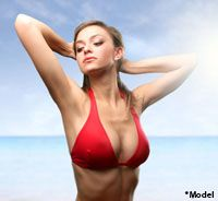 Woman in red bikini top posing in front of ocean