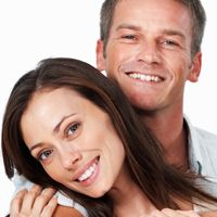 Man and woman smiling following their dentist appointments