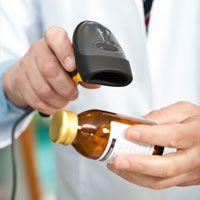 A pharmacist scans a prescription bottle