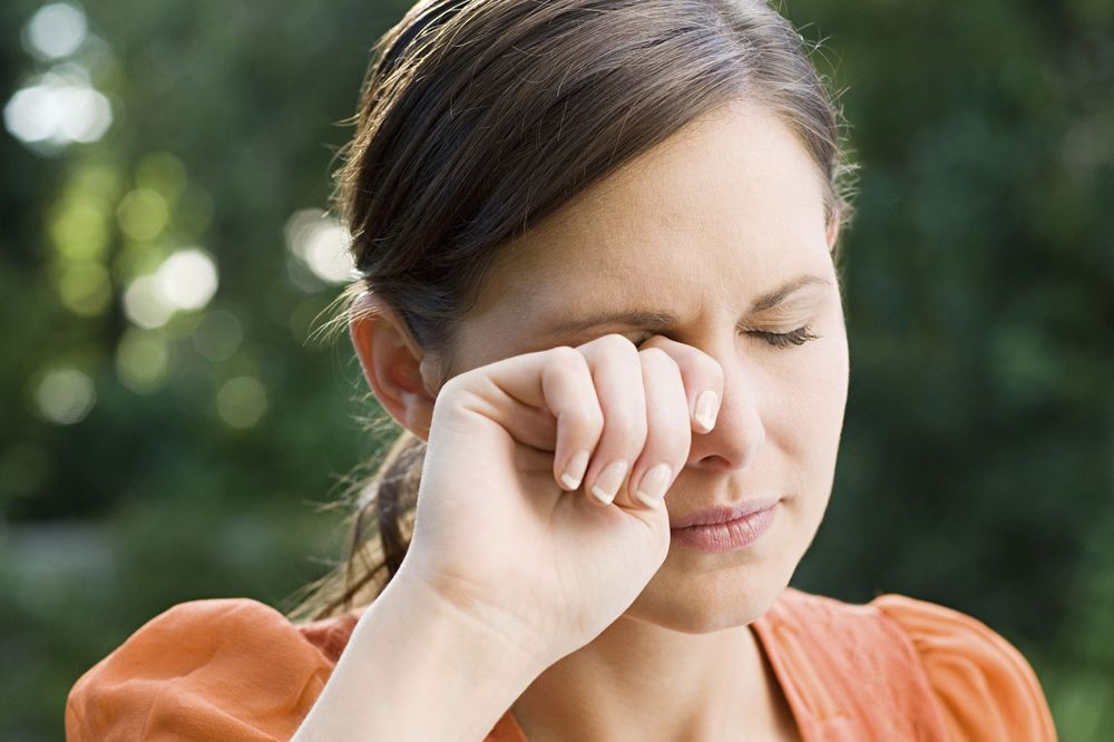 A woman rubs her eye with the back of her hand because it is irritated