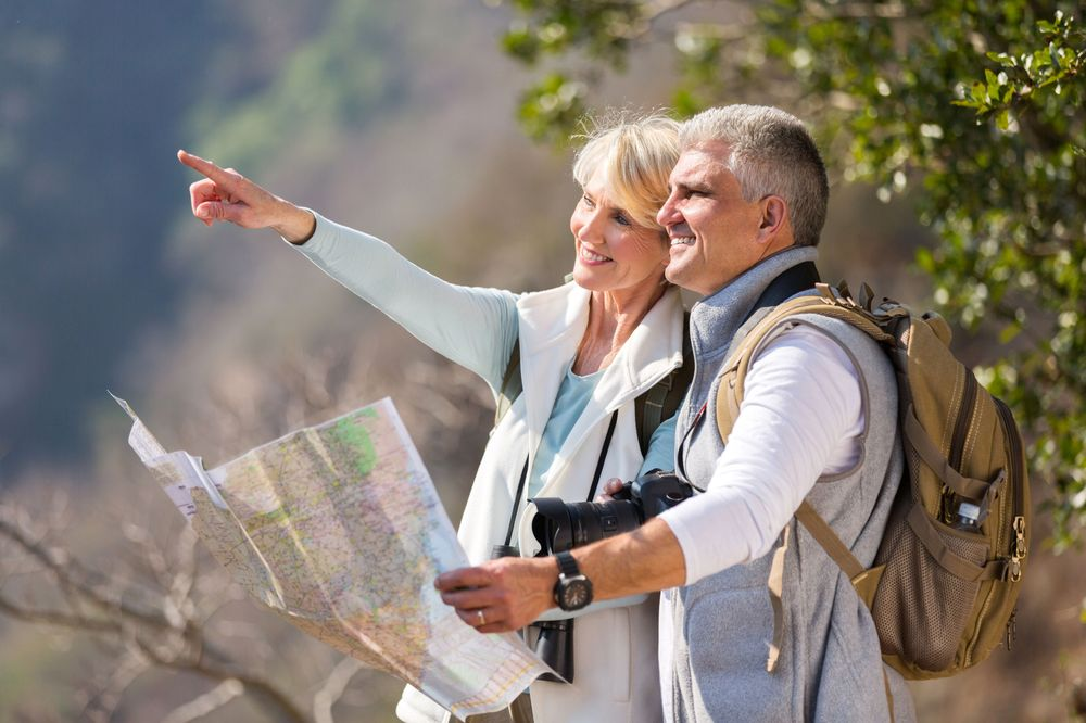 An older couple reads a map while hiking