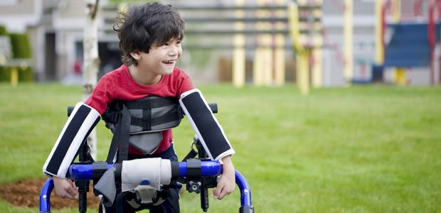 Young boy with cerebral palsy playing outdoors