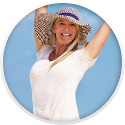Smiling woman in sun hat raising arms over her head