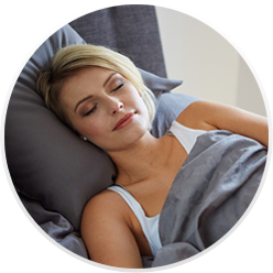 A blonde woman sleeps and recovers from her recent procedure