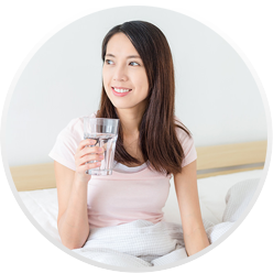 A woman rest in bed and enjoys a glass of water